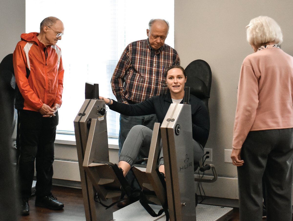 Alisha Van Epps, Fitness Manager and Personal Trainer demonstrating HUR machine to residents